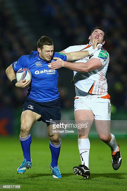 Jimmy Gopperth of Leinster is held up by Ryan Bevington of Ospreys during the Heineken Cup Pool One match between |Leinster and Ospreys at the Royal...