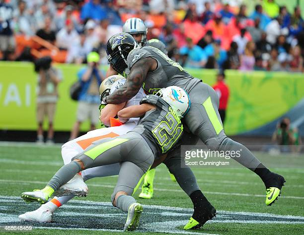Jimmy Graham of the New Orleans Saints and Team Rice is tackled by Terrell Suggs and Brent Grimes of Team Sanders during the 2014 Pro Bowl at Aloha...