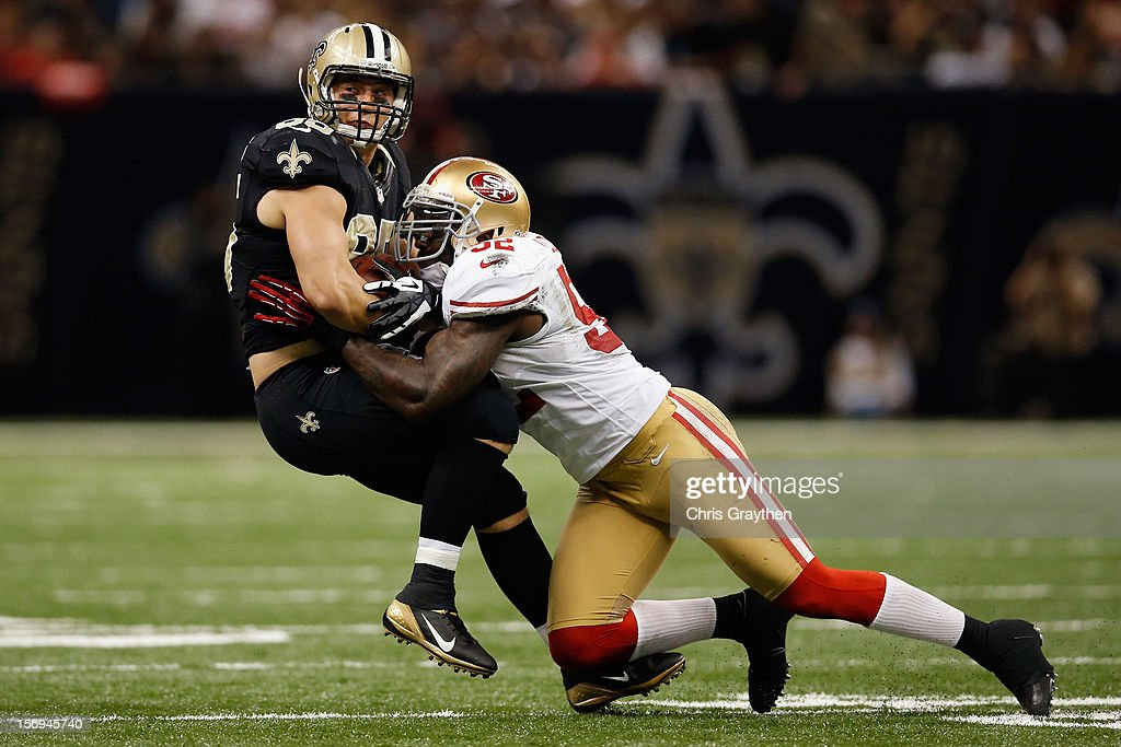 Jimmy Graham #80 of the New Orleans Saints is tackled by Patrick Willis #52 of the San Francisco 49ers at The Mercedes-Benz Superdome on November 25, 2012 in New Orleans, Louisiana.