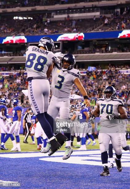 Jimmy Graham of the Seattle Seahawks celebrates his touchdown with teammate quarterback Russell Wilson during the fourth quarter of the game against...