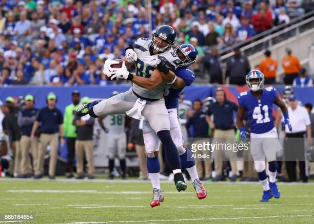 Jimmy Graham of the Seattle Seahawks makes a catch as he is tackled by Avery Moss of the New York Giants during the second quarter of the game at...