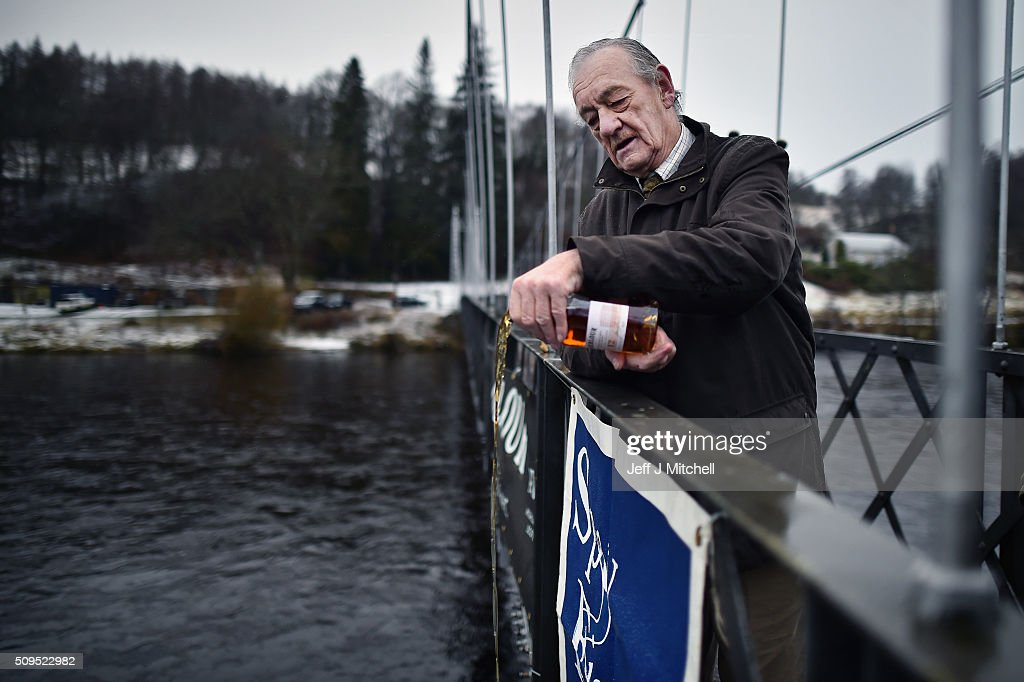 Jimmy Gray MBE pours whiskey during the opening day of the salmon season on the River Spey on February 11, 2016 in Aberlour, Scotland. The annual opening day ceremony took place at Penny Bridge, with the traditional pouring of a bottle of Aberlour twelve year old single malt Scotch whisky into the river.