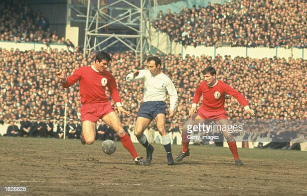 Jimmy Greaves of Tottenham Hotspur sneaks in between Ron Yeats and Tommy Smith of Liverpool during the match between Spurs and Liverpool at White...