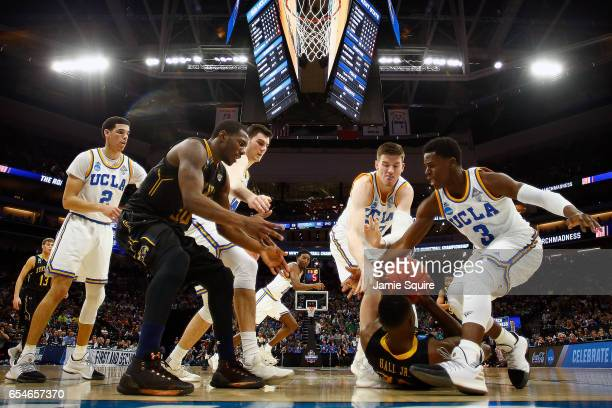 Jimmy Hall of the Kent State Golden Flashes looks to pass as he's defended by TJ Leaf and Aaron Holiday of the UCLA Bruins during the first round of...