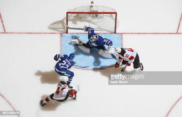 Jimmy Hayes and Adam Henrique of the New Jersey Devils go to the net against Frederik Andersen and Nikita Zaitsev of the Toronto Maple Leafs during...