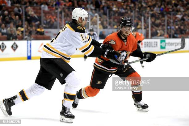 Jimmy Hayes of the Boston Bruins pushes against Nicolas Kerdiles of the Anaheim Ducks during the third period of a game at Honda Center on February...