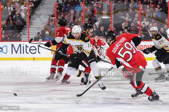 Jimmy Hayes of the Boston Bruins races for the puck against David Dziurzynski of the Ottawa Senators at Canadian Tire Centre on December 27 2015 in...