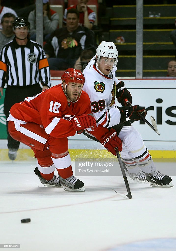 Jimmy Hayes #39 of the Chicago Blackhawks makes a pass during an NHL game as <a gi-track='captionPersonalityLinkClicked' href=/galleries/search?phrase=Ian+White&family=editorial&specificpeople=581742 ng-click='$event.stopPropagation()'>Ian White</a> #18 of the Detroit Red Wings defends at Joe Louis Arena on March 31, 2013 in Detroit, Michigan.