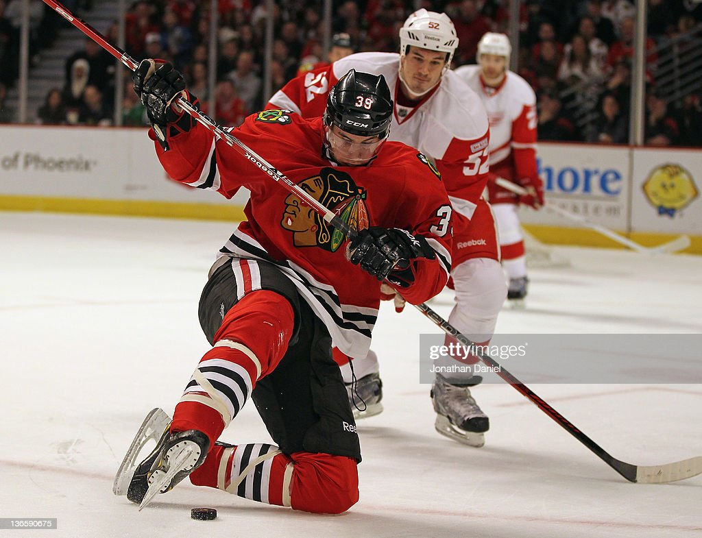 Jimmy Hayes of the Chicago Blackhawks tries to keep his balance and control the puck after being shoved down from behind by Joanthan Ericsson of the...