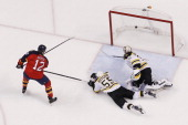 Jimmy Hayes of the Florida Panthers scores a second period goal past goaltender Chad Johnson and Johnny Boychuk of the Boston Bruins at the BBT...