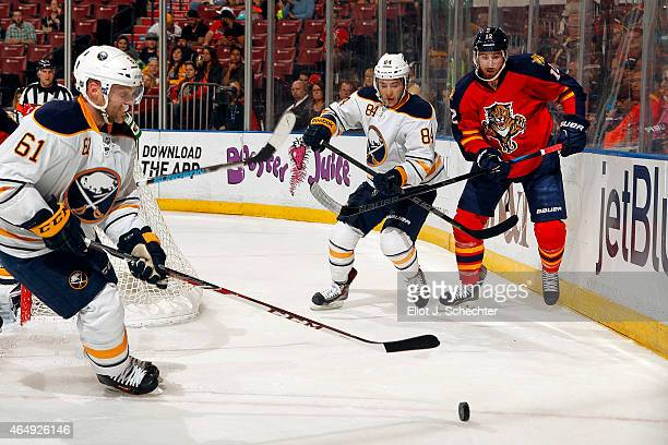 Jimmy Hayes of the Florida Panthers tangles with Philip Varone and Andre Benoit of the Buffalo Sabres at the BBT Center on February 28 2015 in...