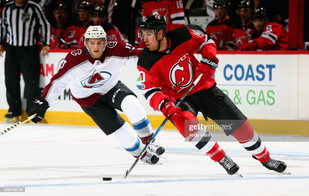 Jimmy Hayes #10 of the New Jersey Devils plays the puck away from Alexander Kerfoot #13 of the Colorado Avalanche during the Devils season opener at Prudential Center on October 7, 2017 in Newark, New Jersey.
