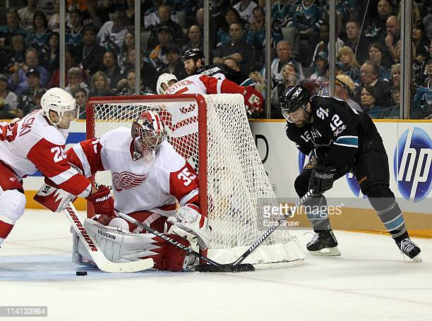 Jimmy Howard and Brian Rafalski of the Detroit Red Wings stop Patrick Marleau of the San Jose Sharks from scoring in Game Seven of the Western...