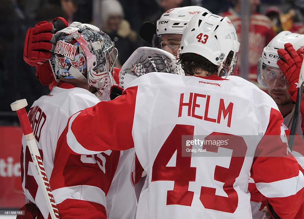 Jimmy Howard #35 and Darren Helm #43 of the Detroit Red Wings celebrate the teams win over the Toronto Maple Leafs during NHL game action March 29, 2014 at the Air Canada Centre in Toronto, Ontario, Canada.