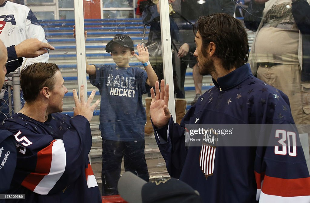 Jimmy Howard of the Detroit Red Wings and Ryan Miller of the Buffalo Sabres greet a young fan following a press conference introducing the 2014 USA Hockey Olympic Team candidates at the Kettler Capitals Iceplex on August 27, 2013 in Arlington, Virginia.