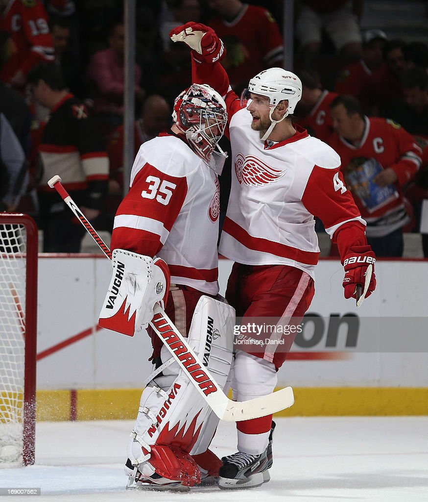 Jimmy Howard #35 of the Detroit Red Wings celebrates a win with teammate Jakub Kindl #4 over the Chicago Blackhawks in Game Two of the Western Conference Semifinals during the 2013 NHL Stanley Cup Playoffs at the United Center on May 18, 2013 in Chicago, Illinois. The Red Wings defeated the Blackhawks 4-1.