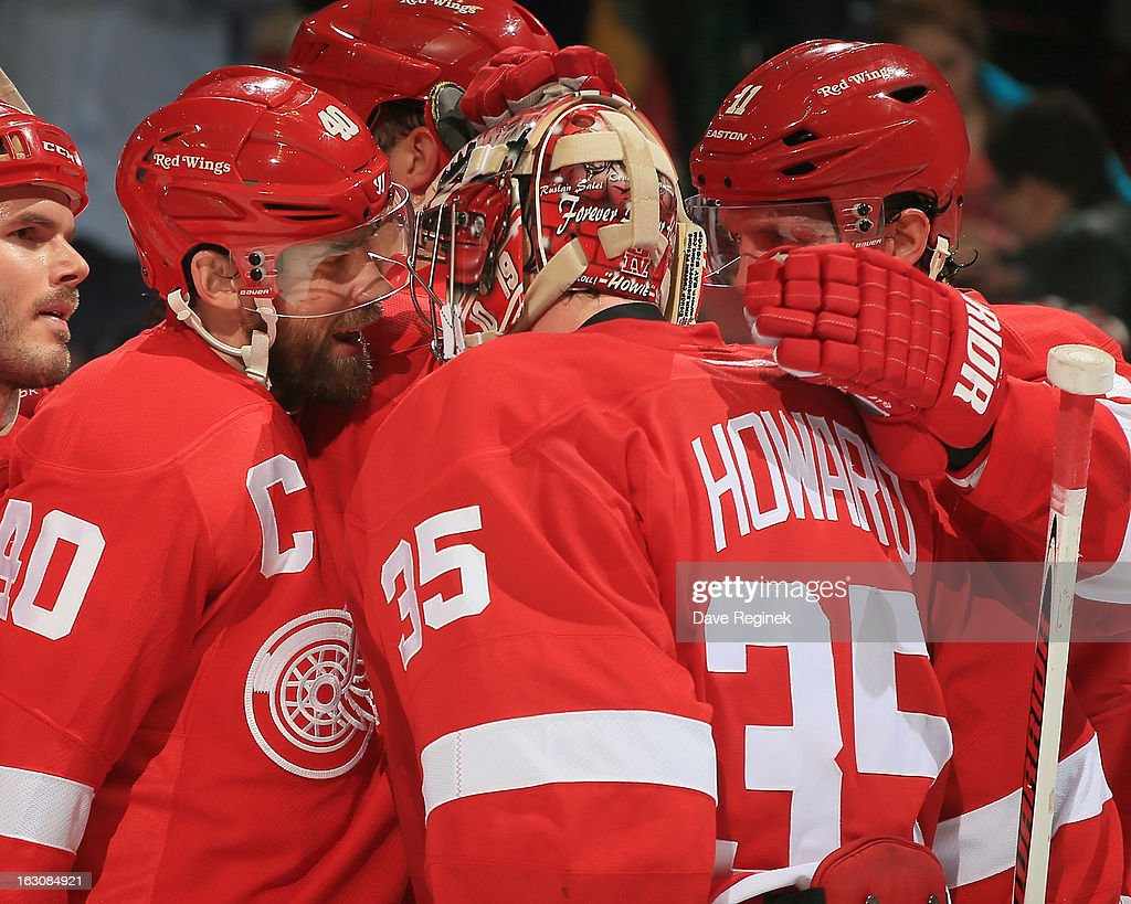 Jimmy Howard of the Detroit Red Wings celebrates the 83 win over the Vancouver Canucks with Henrik Zetterberg and Dan Cleary after a NHL game at Joe...