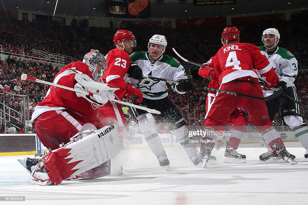<a gi-track='captionPersonalityLinkClicked' href=/galleries/search?phrase=Jimmy+Howard&family=editorial&specificpeople=2118637 ng-click='$event.stopPropagation()'>Jimmy Howard</a> #35 of the Detroit Red Wings covers the puck as teammates <a gi-track='captionPersonalityLinkClicked' href=/galleries/search?phrase=Brian+Lashoff&family=editorial&specificpeople=5529056 ng-click='$event.stopPropagation()'>Brian Lashoff</a> #23 and <a gi-track='captionPersonalityLinkClicked' href=/galleries/search?phrase=Jakub+Kindl&family=editorial&specificpeople=716743 ng-click='$event.stopPropagation()'>Jakub Kindl</a> #4 cover <a gi-track='captionPersonalityLinkClicked' href=/galleries/search?phrase=Antoine+Roussel&family=editorial&specificpeople=4202700 ng-click='$event.stopPropagation()'>Antoine Roussel</a> #21 and <a gi-track='captionPersonalityLinkClicked' href=/galleries/search?phrase=Vernon+Fiddler&family=editorial&specificpeople=208086 ng-click='$event.stopPropagation()'>Vernon Fiddler</a> #38 of the Dallas Stars during an NHL game at Joe Louis Arena on November 7, 2013 in Detroit, Michigan. Dallas defeated Detroit 4-3 in OT