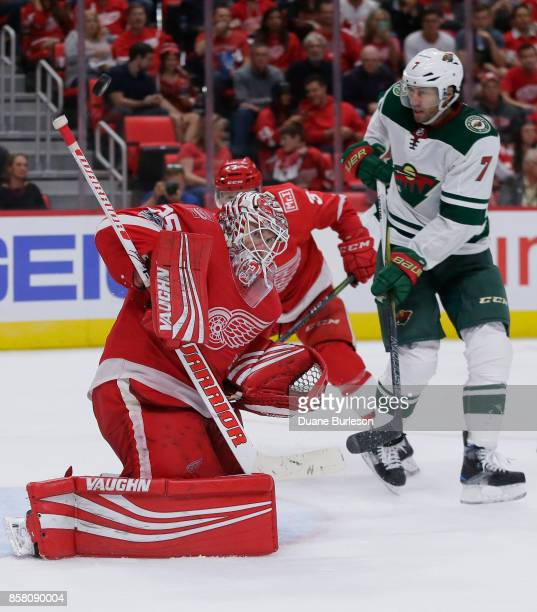 Jimmy Howard of the Detroit Red Wings deflects a shot as Matt Cullen of the Minnesota Wild works in front of the net during the third period at...