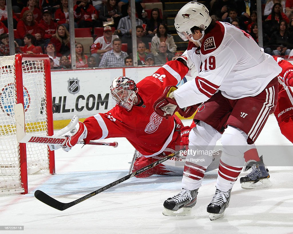 Jimmy Howard #35 of the Detroit Red Wings dives for the puck as Shane Doan #19 of the Phoenix Coyotes back hands it twords the net during a NHL game at Joe Louis Arena on April 22, 2013 in Detroit, Michigan.