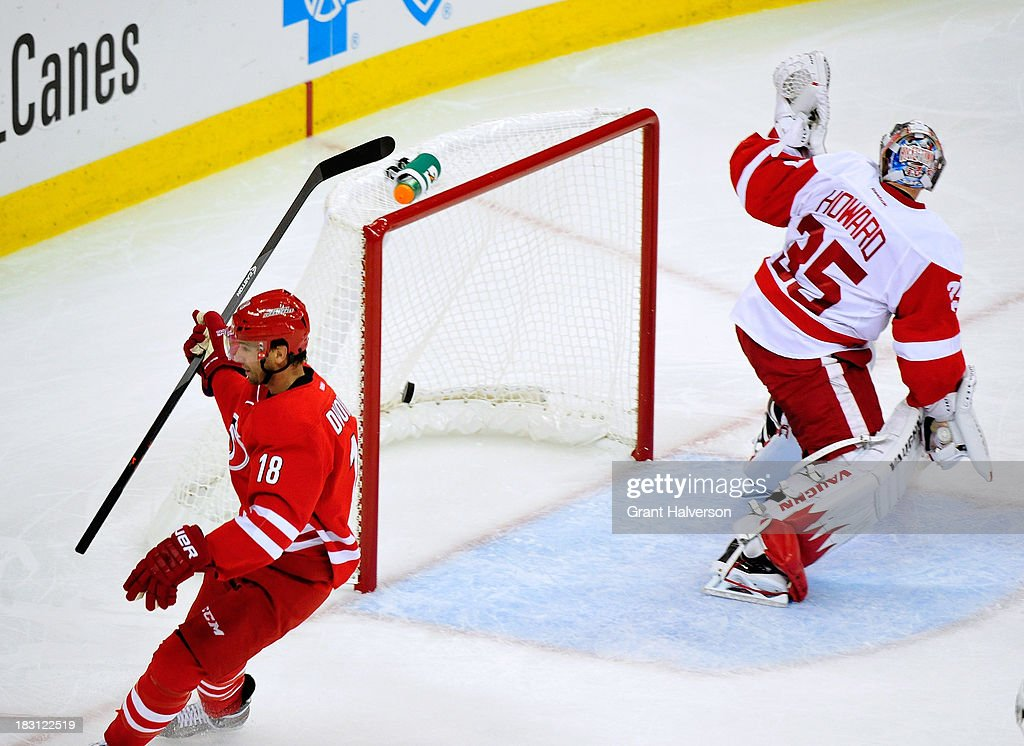 <a gi-track='captionPersonalityLinkClicked' href=/galleries/search?phrase=Jimmy+Howard&family=editorial&specificpeople=2118637 ng-click='$event.stopPropagation()'>Jimmy Howard</a> #35 of the Detroit Red Wings gives up a goal to <a gi-track='captionPersonalityLinkClicked' href=/galleries/search?phrase=Radek+Dvorak&family=editorial&specificpeople=202867 ng-click='$event.stopPropagation()'>Radek Dvorak</a> #18 of the Carolina Hurricanes during the first period at PNC Arena on October 4, 2013 in Raleigh, North Carolina.