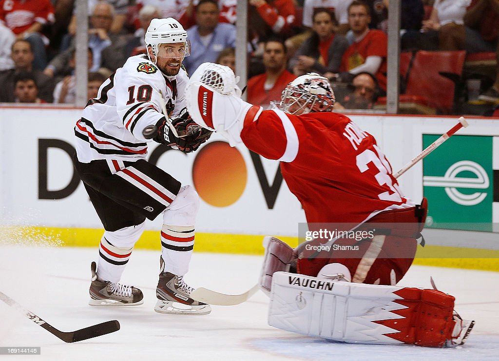 <a gi-track='captionPersonalityLinkClicked' href=/galleries/search?phrase=Jimmy+Howard&family=editorial&specificpeople=2118637 ng-click='$event.stopPropagation()'>Jimmy Howard</a> #35 of the Detroit Red Wings grabs the puck before <a gi-track='captionPersonalityLinkClicked' href=/galleries/search?phrase=Patrick+Sharp&family=editorial&specificpeople=206279 ng-click='$event.stopPropagation()'>Patrick Sharp</a> #10 of the Chicago Blackhawks gets his stick on it during the third period in Game Three of the Western Conference Semifinals during the 2013 NHL Stanley Cup Playoffs at Joe Louis Arena on May 20, 2013 in Detroit, Michigan. Detroit won the game 3-1 to take a 2-1 series lead.