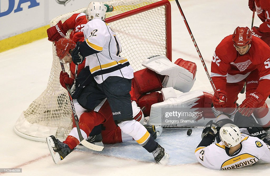 <a gi-track='captionPersonalityLinkClicked' href=/galleries/search?phrase=Jimmy+Howard&family=editorial&specificpeople=2118637 ng-click='$event.stopPropagation()'>Jimmy Howard</a> #35 of the Detroit Red Wings keeps the puck out of the net surrounded by teammates <a gi-track='captionPersonalityLinkClicked' href=/galleries/search?phrase=Jonathan+Ericsson&family=editorial&specificpeople=2538498 ng-click='$event.stopPropagation()'>Jonathan Ericsson</a> #52 and <a gi-track='captionPersonalityLinkClicked' href=/galleries/search?phrase=Brad+Stuart+-+Ice+Hockey+Player&family=editorial&specificpeople=213995 ng-click='$event.stopPropagation()'>Brad Stuart</a> #23 along with <a gi-track='captionPersonalityLinkClicked' href=/galleries/search?phrase=Mike+Fisher&family=editorial&specificpeople=204732 ng-click='$event.stopPropagation()'>Mike Fisher</a> #12 and <a gi-track='captionPersonalityLinkClicked' href=/galleries/search?phrase=Patric+Hornqvist&family=editorial&specificpeople=1966879 ng-click='$event.stopPropagation()'>Patric Hornqvist</a> #27 of the Nashville Predators during Game Three of the Western Conference Quarterfinals during the 2012 NHL Stanley Cup Playoffs at Joe Louis Arena on April 15, 2012 in Detroit, Michigan. Nashville won the game 3-2 and lead the series 2-1.