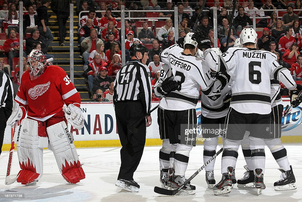 Jimmy Howard #35 of the Detroit Red Wings looks away as Matt Greene #2, Jake Muzzin #6, Jarret Stoll #28 and Trevor Lewis #22 of the Los Angeles Kings congratulate teammate Kyle Clifford #13 after scoring a goal during a NHL game at Joe Louis Arena on April 24, 2013 in Detroit, Michigan.