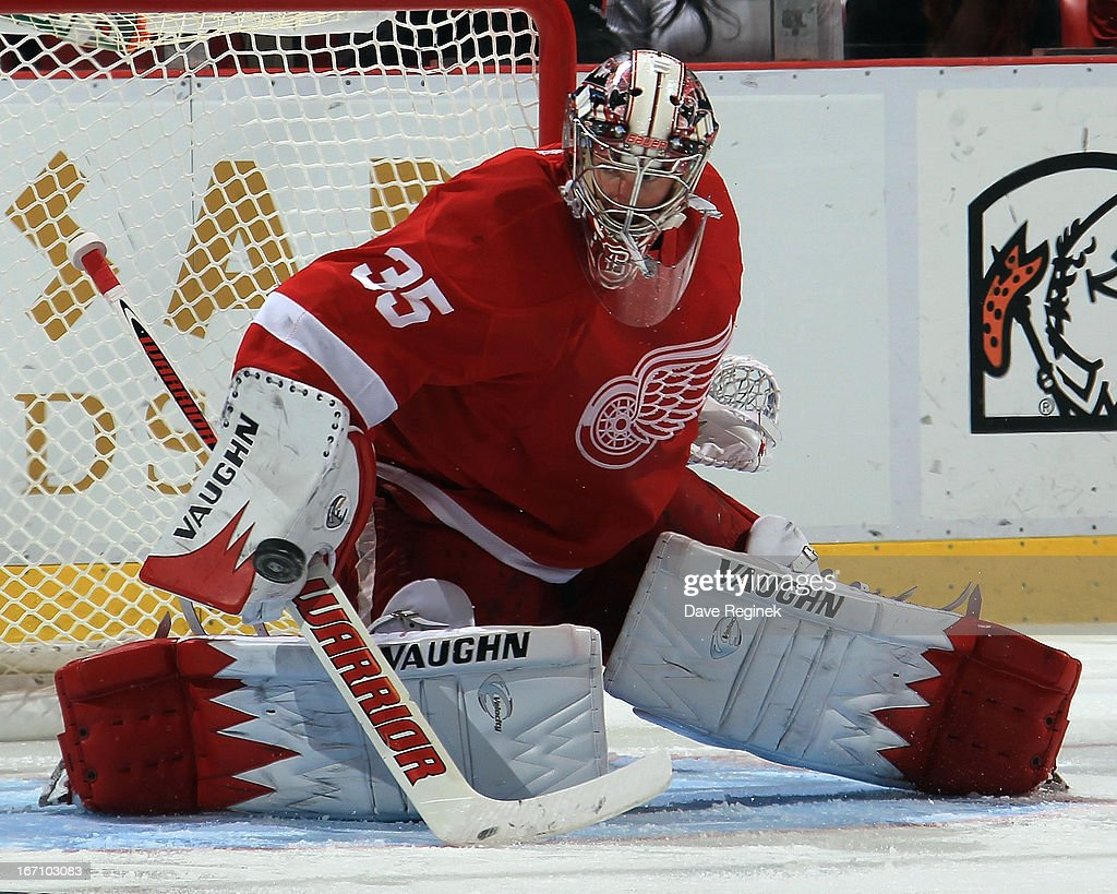Jimmy Howard #35 of the Detroit Red Wings makes a blocker save during a NHL game against the San Jose Sharks at Joe Louis Arena on April 11, 2013 in Detroit, Michigan. San Jose defeated Detroit 3-2 in a shoot-out