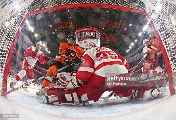 Jimmy Howard of the Detroit Red Wings makes a kick save as teammate Joakim Andersson defends against the attack of PierreEdouard Bellemare of the...