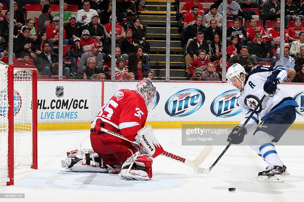 <a gi-track='captionPersonalityLinkClicked' href=/galleries/search?phrase=Jimmy+Howard&family=editorial&specificpeople=2118637 ng-click='$event.stopPropagation()'>Jimmy Howard</a> #35 of the Detroit Red Wings makes a save as <a gi-track='captionPersonalityLinkClicked' href=/galleries/search?phrase=Bryan+Little&family=editorial&specificpeople=540533 ng-click='$event.stopPropagation()'>Bryan Little</a> #18 of the Winnipeg Jets crashes the net during an NHL game at Joe Louis Arena on November 12, 2013 in Detroit, Michigan.