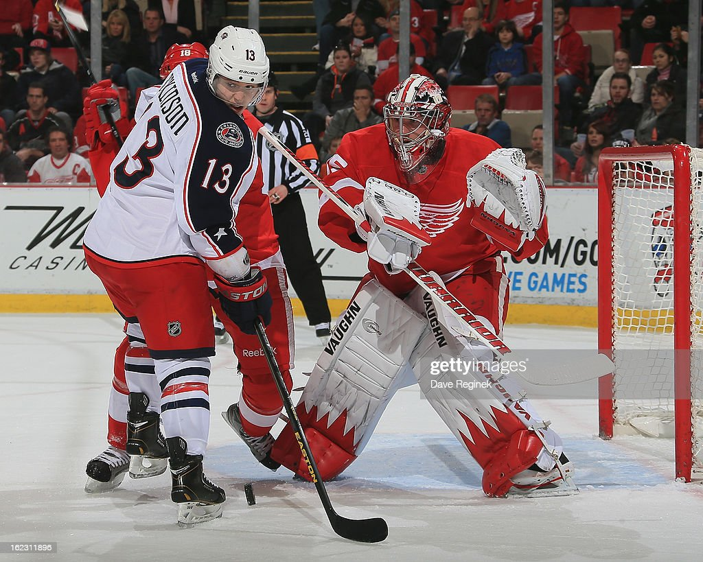 Jimmy Howard of the Detroit Red Wings makes a save as Cam Atkinson of the Columbus Blue Jackets looks for the puck during a NHL game at Joe Louis...