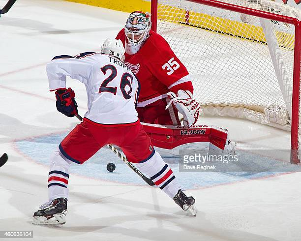 Jimmy Howard of the Detroit Red Wings makes a save as Corey Tropp of the Columbus Blue Jackets goes after the loose puck during a NHL game on...