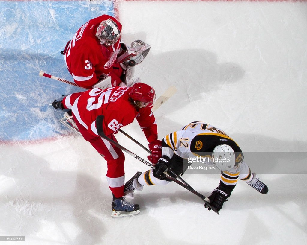 Jimmy Howard #35 of the Detroit Red Wings makes a save as teammate Danny DeKeyser #65 battles with Jarome Iginla #12 of the Boston Bruins in front of the net during Game Three of the First Round of the 2014 Stanley Cup Playoffs on April 22, 2014 at Joe Louis Arena in Detroit, Michigan.