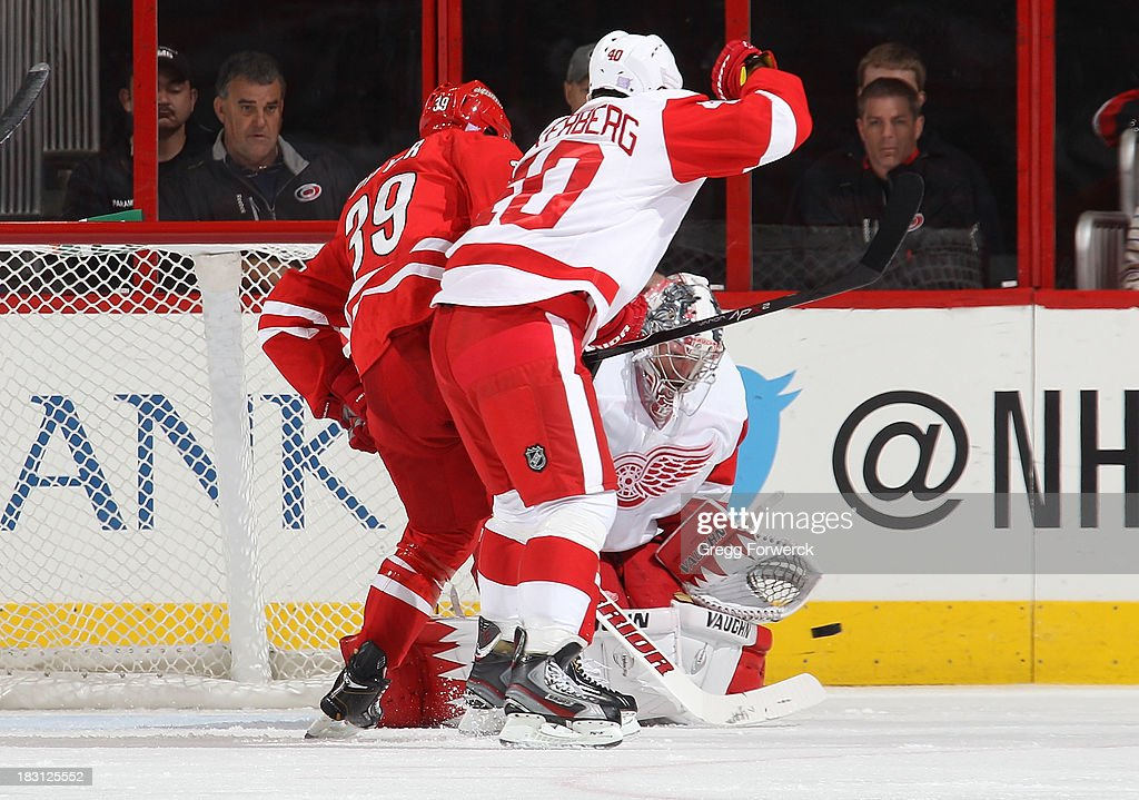 <a gi-track='captionPersonalityLinkClicked' href=/galleries/search?phrase=Jimmy+Howard&family=editorial&specificpeople=2118637 ng-click='$event.stopPropagation()'>Jimmy Howard</a> #35 of the Detroit Red Wings makes a save as teammate <a gi-track='captionPersonalityLinkClicked' href=/galleries/search?phrase=Henrik+Zetterberg&family=editorial&specificpeople=201520 ng-click='$event.stopPropagation()'>Henrik Zetterberg</a> #40 battles with Patrick Dwyer #39 of the Carolina Hurricanes during an NHL game on October 4, 2013 in the home opener at PNC Arena in Raleigh, North Carolina.
