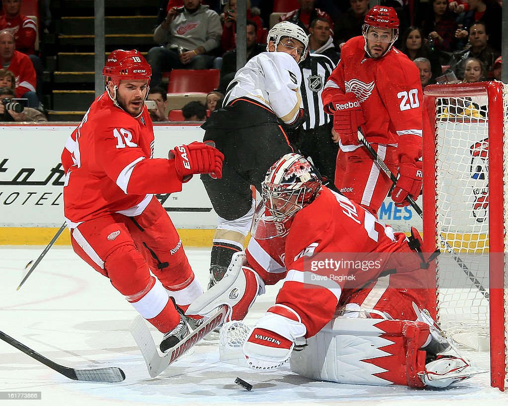 Jimmy Howard #35 of the Detroit Red Wings makes a save during a NHL game against the Anaheim Ducks as teamate Ian White #18 covers the front of the net on February 15, 2013 at Joe Louis Arena in Detroit, Michigan.