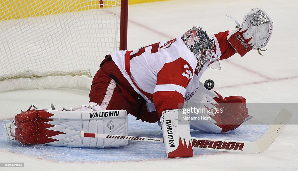 <a gi-track='captionPersonalityLinkClicked' href=/galleries/search?phrase=Jimmy+Howard&family=editorial&specificpeople=2118637 ng-click='$event.stopPropagation()'>Jimmy Howard</a> #35 of the Detroit Red Wings makes a save in first period action in an NHL game against the Winnipeg Jets at the MTS Centre on November 4, 2013 in Winnipeg, Manitoba, Canada.