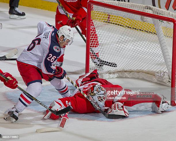 Jimmy Howard of the Detroit Red Wings makes a save on Corey Tropp of the Columbus Blue Jackets during a NHL game on December 16 2014 at Joe Louis...