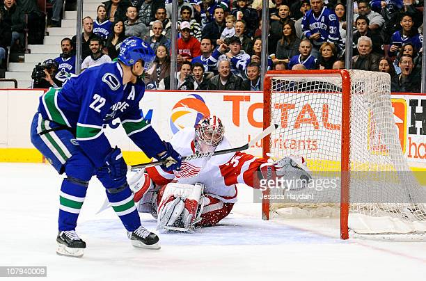 Jimmy Howard of the Detroit Red Wings makes a save on Daniel Sedin of the Vancouver Canucks during their game at Rogers Arena on January 8 2011 in...