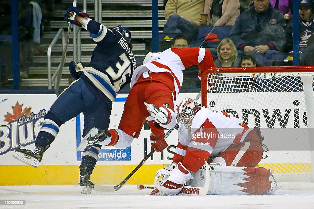Jimmy Howard #35 of the Detroit Red Wings makes a save on Jonathan Audy-Marchessault #36 of the Columbus Blue Jackets as Kent Huskins #3 of the Detroit Red Wings trips over Howard during the first period on February 2, 2013 at Nationwide Arena in Columbus, Ohio.