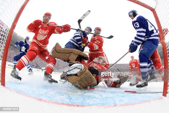 Jimmy Howard of the Detroit Red Wings makes a spinning arm save as teammates Daniel Cleary and Kyle Quincey defend against David Clarkson and Nazem...