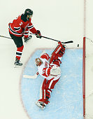 Jimmy Howard of the Detroit Red Wings makes the save on John Moore of the New Jersey Devils at the Prudential Center on December 11 2015 in Newark...