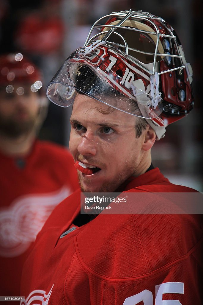 Jimmy Howard #35 of the Detroit Red Wings pauses by the bench during a NHL game against the San Jose Sharks at Joe Louis Arena on April 11, 2013 in Detroit, Michigan. San Jose defeated Detroit 3-2 in a shoot-out