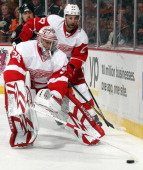 Jimmy Howard of the Detroit Red Wings plays the puck behind the net as teammate Kyle Quincey follows during the game against the Detroit Red Wings on...