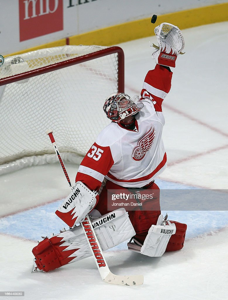 Jimmy Howard of the Detroit Red Wings reaches for the puck against the Chicago Blackhawks at the United Center on April 12 2013 in Chicago Illinois