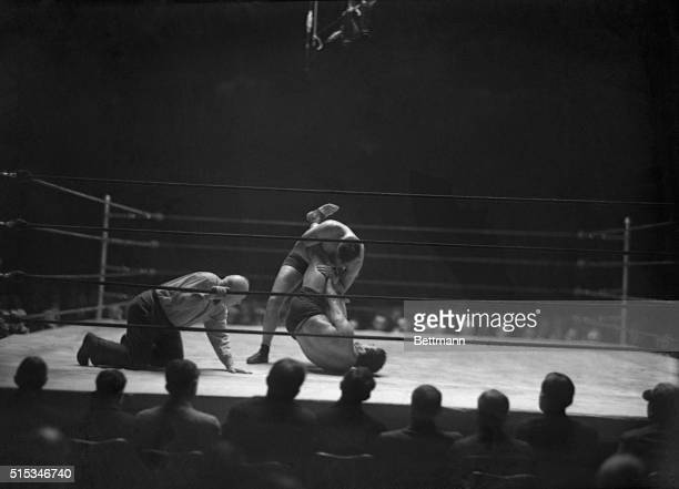 Jimmy Mc Millen standing trying to pin Londos shoulders to the man with the excruciatingly painful 'leg split' The champion broken the hold however...