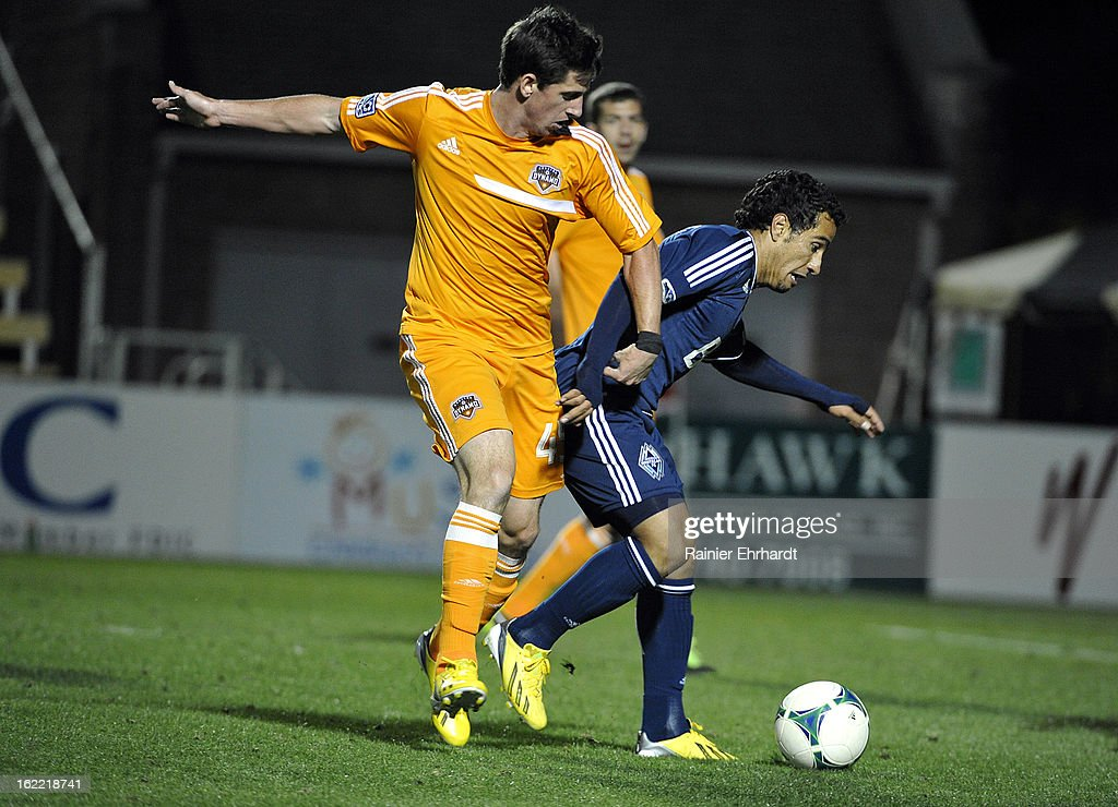 Jimmy Nealis #45 of the Houston Dynamo and Camilo Sanvezzo #7 of the Vancouver Whitecaps FC battle for the ball during the second half of a game at Blackbaud Stadium on February 20, 2013 in Charleston, North Carolina.