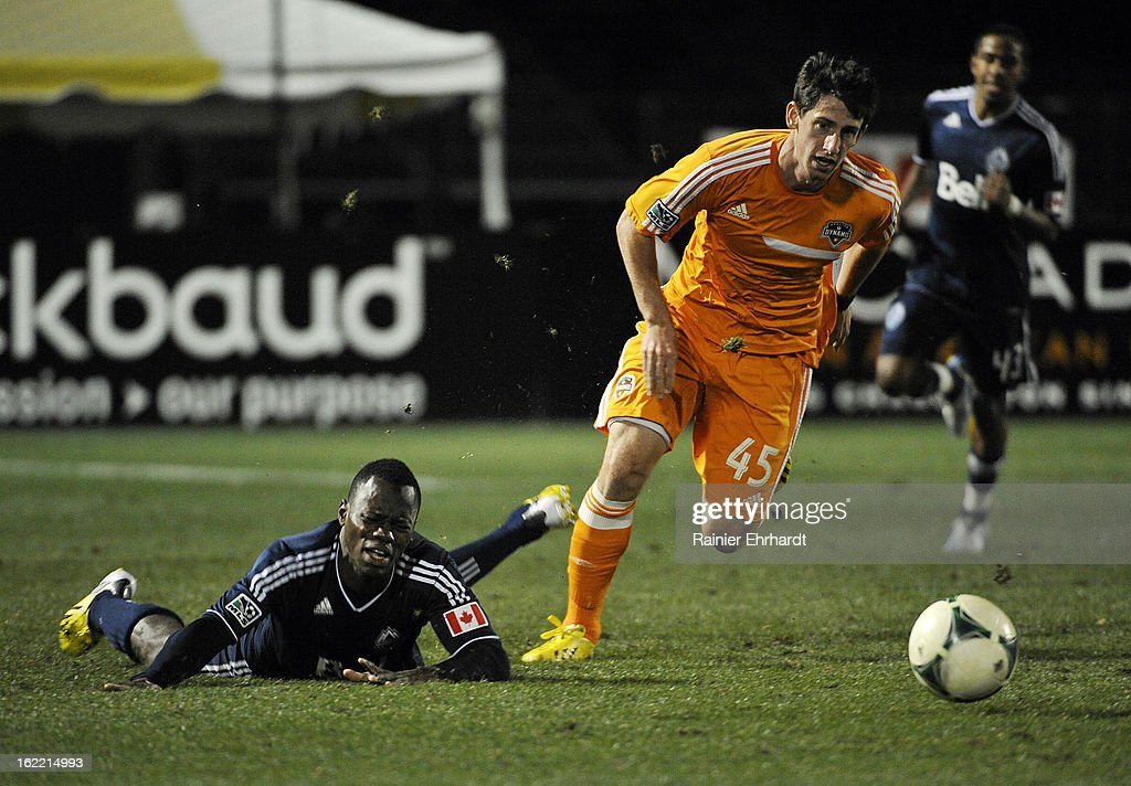 Jimmy Nealis #45 of the Houston Dynamo runs with the ball as Dever Orgill #42 of the Vancouver Whitecaps FC falls during the second half of a game on February 20, 2013 in Charleston, North Carolina.