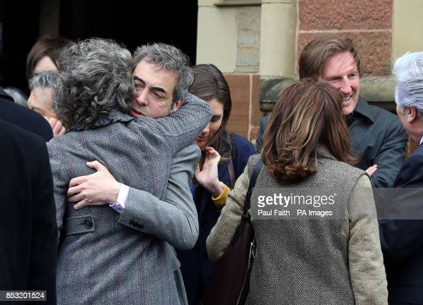 Jimmy Nesbitt hugs Robina the wife of Jimmy Ellis following his funeral which took place at St Mark's Church on Holywood Road east Belfast