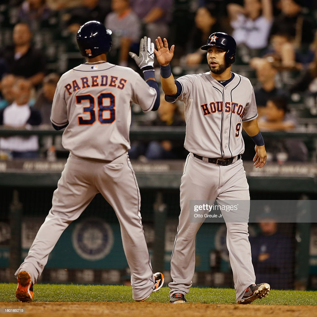 Jimmy Paredes #38 of the Houston Astros is congratulated by Marwin Gonzalez #9 after scoring on a single by Jonathan Villar in the ninth inning against the Seattle Mariners at Safeco Field on September 9, 2013 in Seattle, Washington.